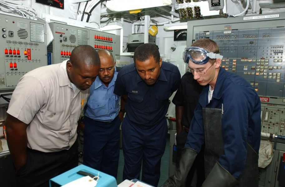 US Navy 080703-N-8943B-004 Gas Systems Turbine (Mechanical) Fireman James Smith explains an engineering system to members of the St. Lucia Marine Police