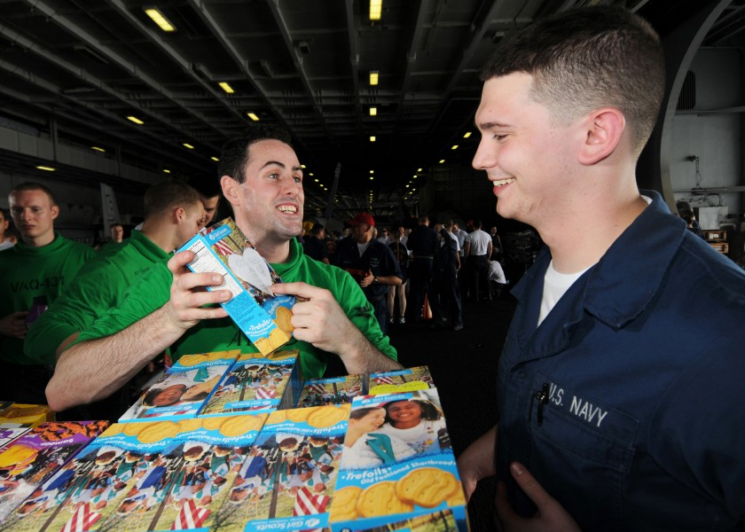 US Navy 080726-N-9898L-007 Aviation Electrician's Mate 3rd Class Stephan Riggs shows Ship's Serviceman Seaman Kevin Simak a note attached to a box of Girl Scouts cookies