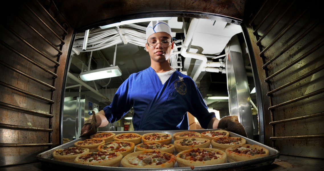 US Navy 080809-N-7981E-082 Culinary Specialist 3rd Class Gabriel Common, from Basile, La., takes pizzas out of the oven in the aft galley aboard the Nimitz-class aircraft carrier USS Abraham Lincoln (CVN 72)