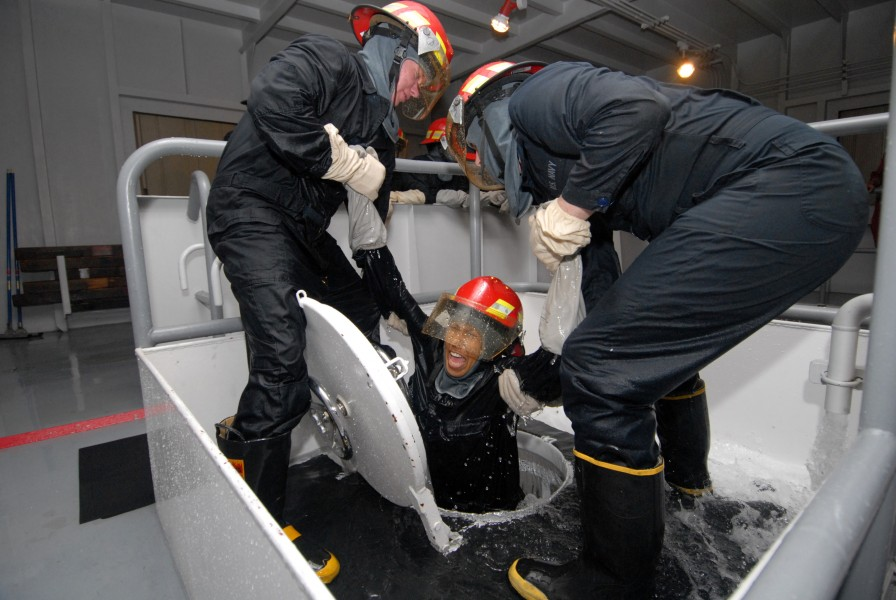 US Navy 080819-N-6936D-124 Sailors assigned to the amphibious assault ship USS Essex (LHD 2) work together to help a shipmate exit from a flooding space