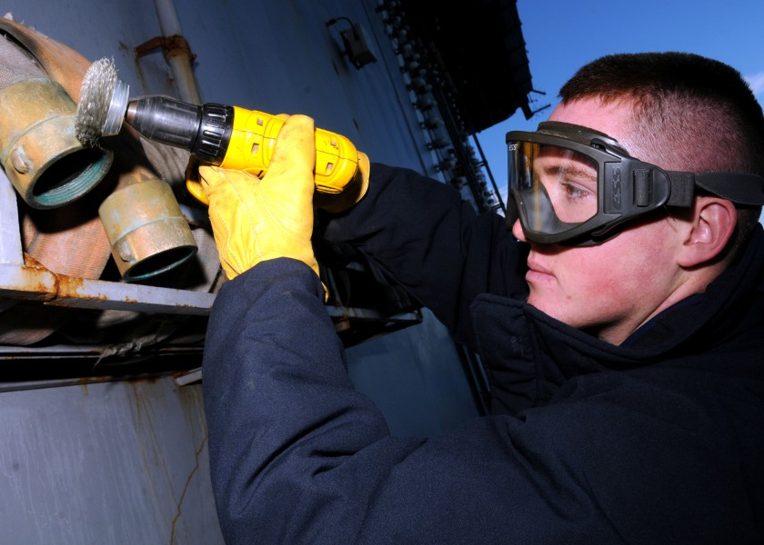 US Navy 081201-N-9898L-068 viation Boatswain's Mate Airman Mitchell Larson removes corrosion from a fire hose