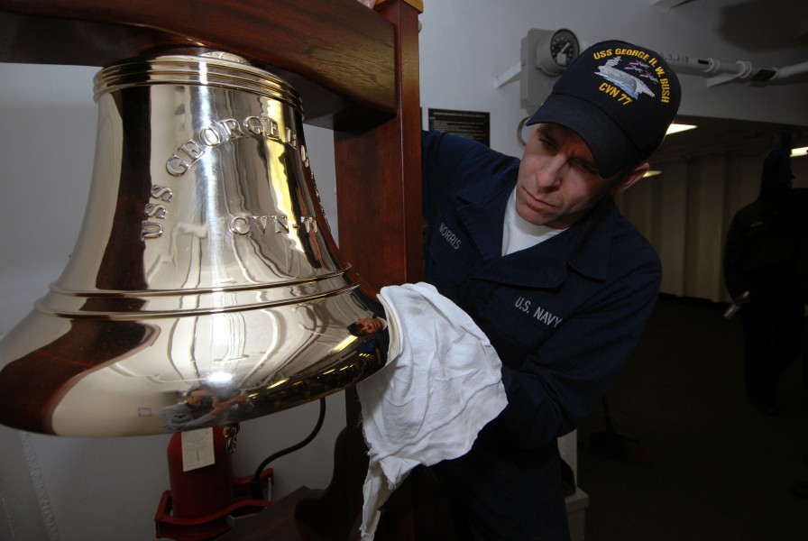 US Navy 090107-N-5658B-011 Boatswain's Mate Seaman Apprentice Charles Norris polishes a bell aboard the ceremonial quarterdeck of USS George H.W. Bush (CVN 77)