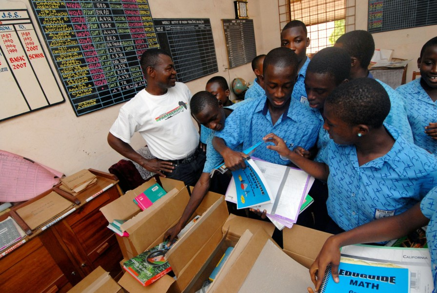 US Navy 090304-N-1688B-335 Cameroon Navy Lt. Cmdr. Hamadou Lame, left, watches as students from the Naval Base Basic School in Sekondi, Ghana receive school books and supplies donated by Project Handclasp