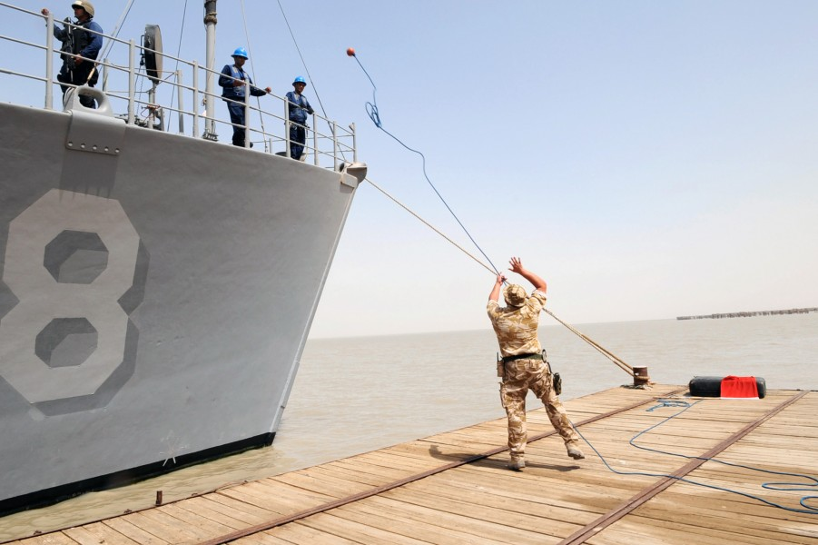 US Navy 090630-N-6814F-057 British Royal Navy Leading Seaman Lee Noak throws a messenger line to the deck of mine countermeasure ship USS Scout (MCM 8) as it pulls into Umm Qasr, Iraq