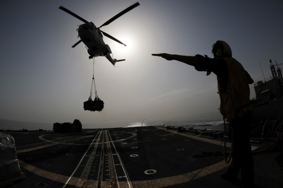US Navy 090805-N-6814F-269 Seaman Jared Hanschu directs an SA-330 Puma helicopter to drop a pallet onto the flight deck of the guided-missile cruiser USS Anzio (CG 68)