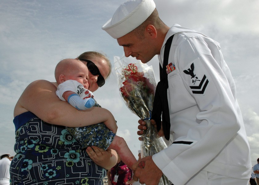 US Navy 090828-N-5292M-521 Damage Controlman 2nd Class Jeff McClure, assigned to the guided-missile destroyer USS Laboon (DDG 58), greets his 5-month-old son for the first time at Naval Station Norfolk, Va