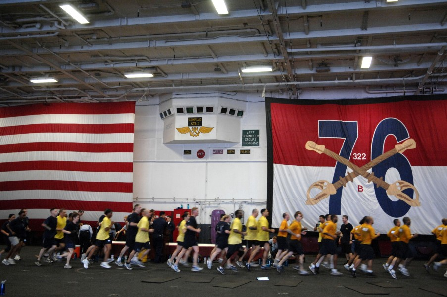 US Navy 090913-N-9818V-065 Sailors aboard the aircraft carrier USS Ronald Reagan (CVN 76) conduct morning physical training in the hangar bay of the ship