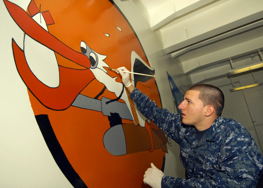 US Navy 091013-N-9793B-025 Seaman Jonathan Robles, assigned to the deck department of the aircraft carrier USS George H.W. Bush (CVN 77), adds the finishing touches to a mural