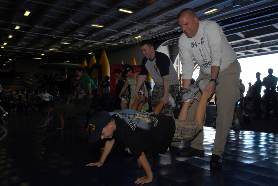 US Navy 091016-N-5586R-177 Sailors and Tiger Cruise participants compete in a wheelbarrow race aboard the aircraft carrier USS Ronald Reagan (CVN 76)