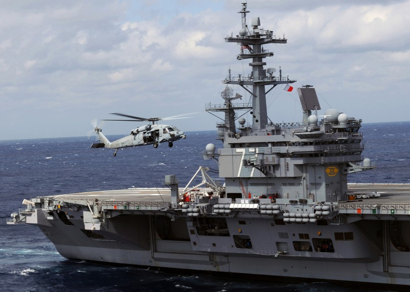 US Navy 100303-N-3885H-172 An MH-60S Sea Hawk helicopter flies alongside USS George H.W. Bush (CVN 77)
