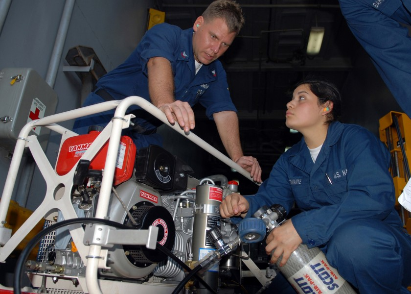 US Navy 100304-N-6692A-041 Damage Controlman 2nd Class Kevin L. Clark instructs Damage Controlman Fireman Recruit Marcela R. Bustamante on charging an oxygen bottle for self-contained breathing apparatus