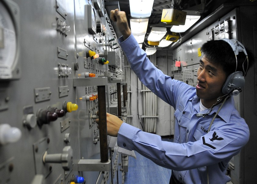 US Navy 100409-N-4774B-620 Electrician's Mate 3rd Class Ju Kim, from Alexandria, Virginia, operates controls in Main Engine Room Two aboard the guided-missile cruiser USS Bunker Hill (CG 52)