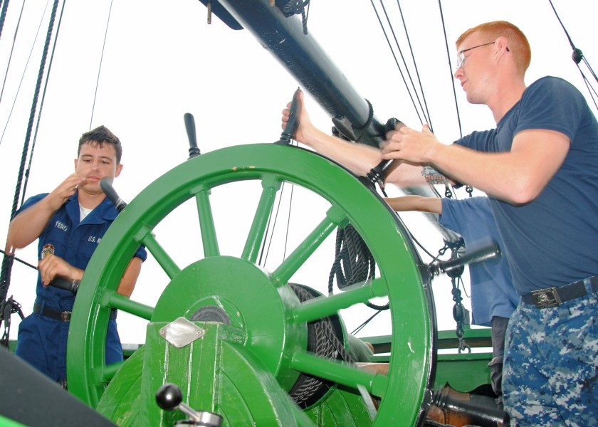 US Navy 100714-N-5647H-170 Fireman Apprentice Esteban Quintero, left, and Airman Dylan Roberts, both assigned to USS Constitution, steer the rudder aboard the Friendship of Salem