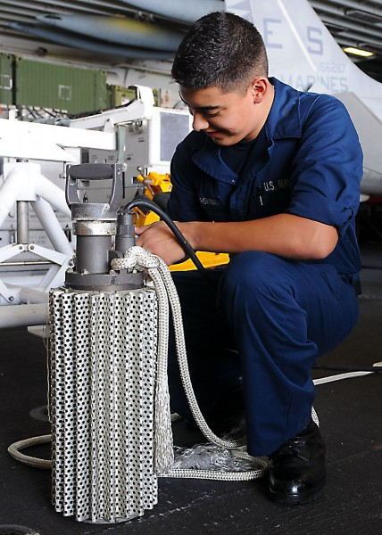 US Navy 101116-N-2908M-009 Damage Controlman Fireman Luis Baezarohana attaches a line to an electrical submersible pump to prepare for a damage con