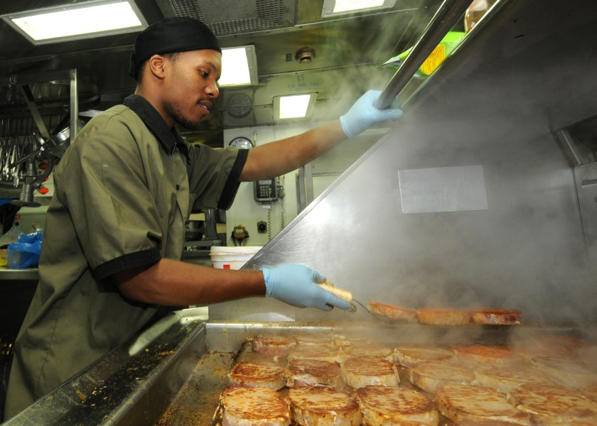 US Navy 110124-N-9793B-024 Culinary Specialist Seaman Diante A. Johnson prepares pork chops in the ship's galley