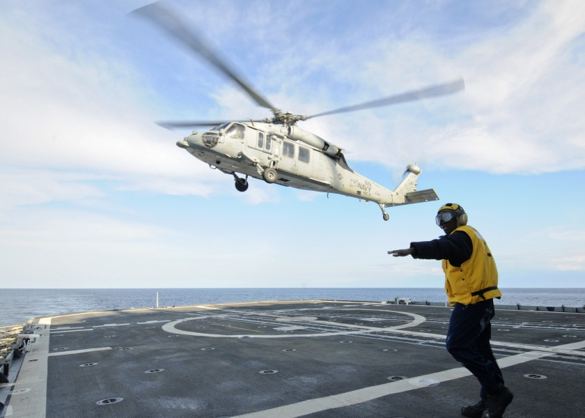 US Navy 110217-N-9793B-186 Boatswain's Mate 2nd Class Tyrone Williams directs an MH-60S Sea Hawk helicopter assigned to Helicopter Sea Combat (HSC)