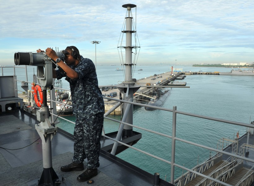 US Navy 110312-N-0864H-280 Operations Specialist 3rd Class Anthony Wilson looks through the