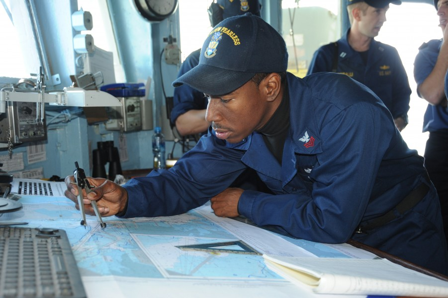 US Navy 110320-N-8497H-009 Quartermaster 1st Class Don Holt uses a protractor to check the ship's course aboard the mine countermeasures ship USS A
