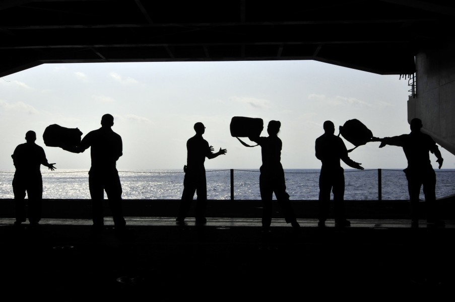 US Navy 110414-N-DM338-087 Sailors pass chemical, biological and radiological kits during a working party in the hangar bay of the aircraft carrier