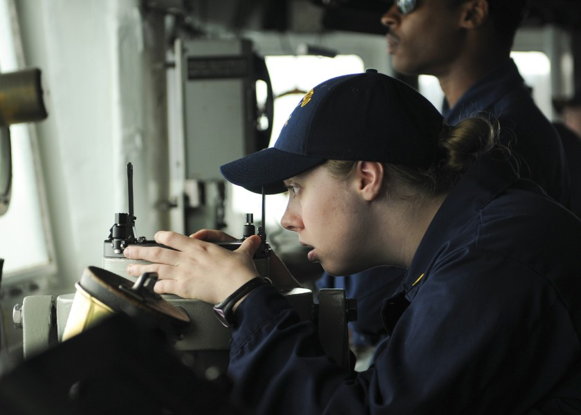 US Navy 110515-N-YM590-102 Ensign Meredith C. Manuel peers through a telescopic alidade on the bridge aboard the guided-missile cruiser USS Anzio (