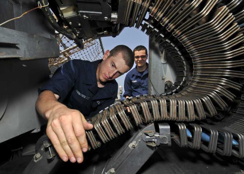 US Navy 110618-N-YM590-079 Gunner's Mate Seaman Ryan Synowietz performs maintenance on a MK-38 25mm gun system aboard the guided-missile cruiser US