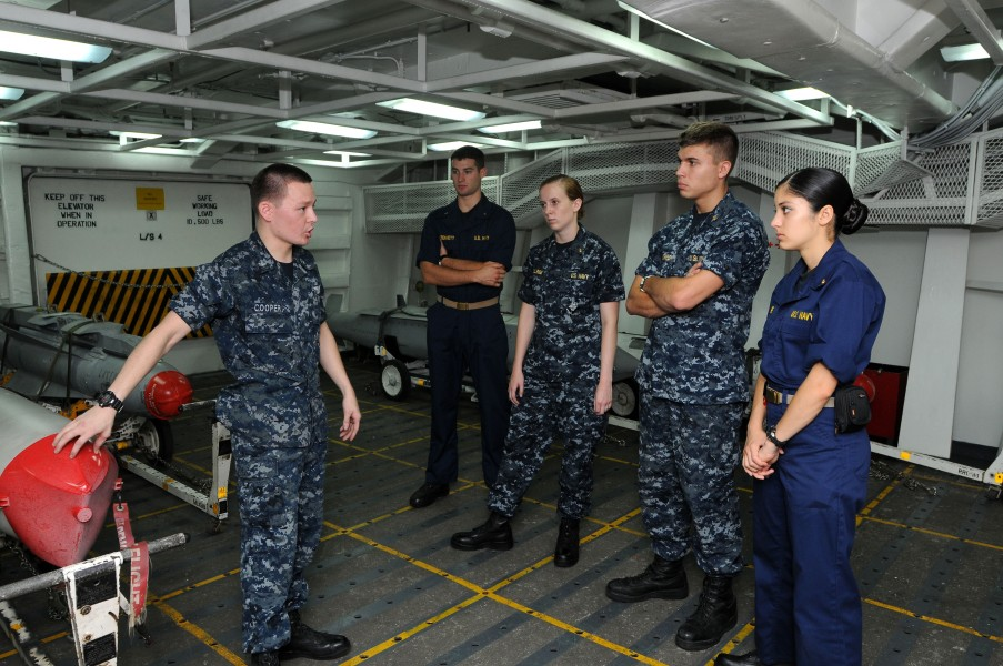 US Navy 110705-N-NB544-031 Aviation Ordnanceman 2nd Class Daniel Cooper, left, explains the different types of ordnance to midshipmen aboard aircra