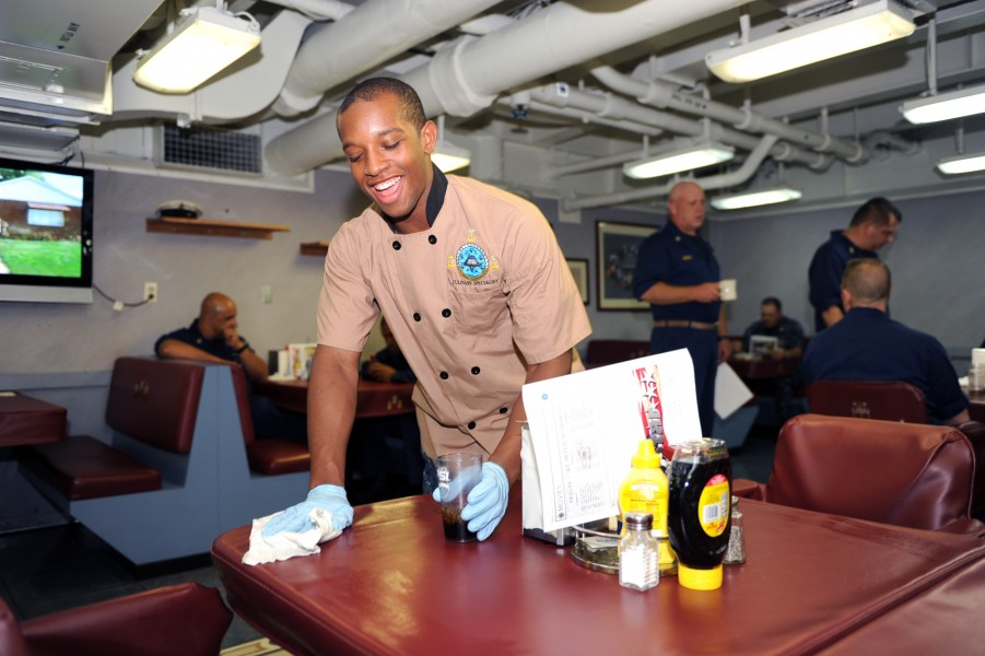 US Navy 110715-N-AU622-044 Airman Apprentice Justin Williams, from St. Louis, Mo., wipes a table in the chief's mess aboard the aircraft carrier US