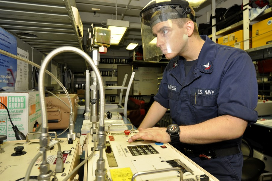 US Navy 110719-N-ZZ999-032 Machinist's Mate 2nd Class Matthew Lafleur, from Pequea, Pa., calibrates a pressure switch aboard the aircraft carrier U