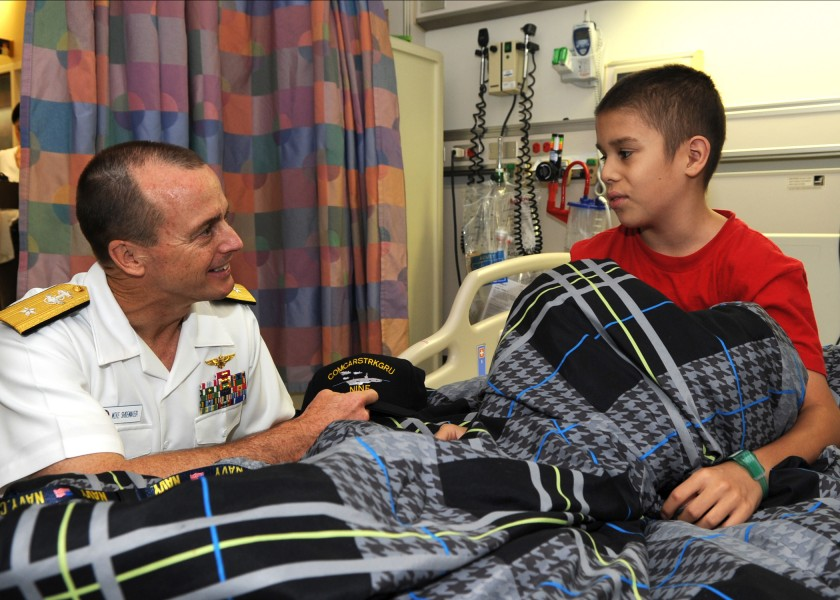 US Navy 110726-N-QN972-003 Rear Adm. Troy Shoemaker, commander of the Abraham Lincoln Carrier Strike Group, presents a ball cap to a patient at the
