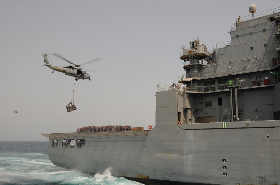 US Navy 110812-N-XQ375-446 An SH-60 Sea Hawk helicopter transfers pallets of stores from the Military Sealift Command dry cargo and ammunition ship