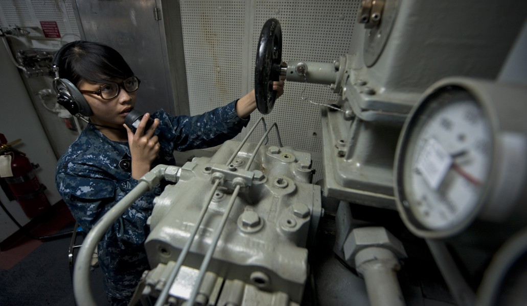 US Navy 111003-N-TU221-044 Seaman Mafe Sabar mans a sound-powered telephone inside the aft steering engine room aboard the Nimitz-class aircraft ca