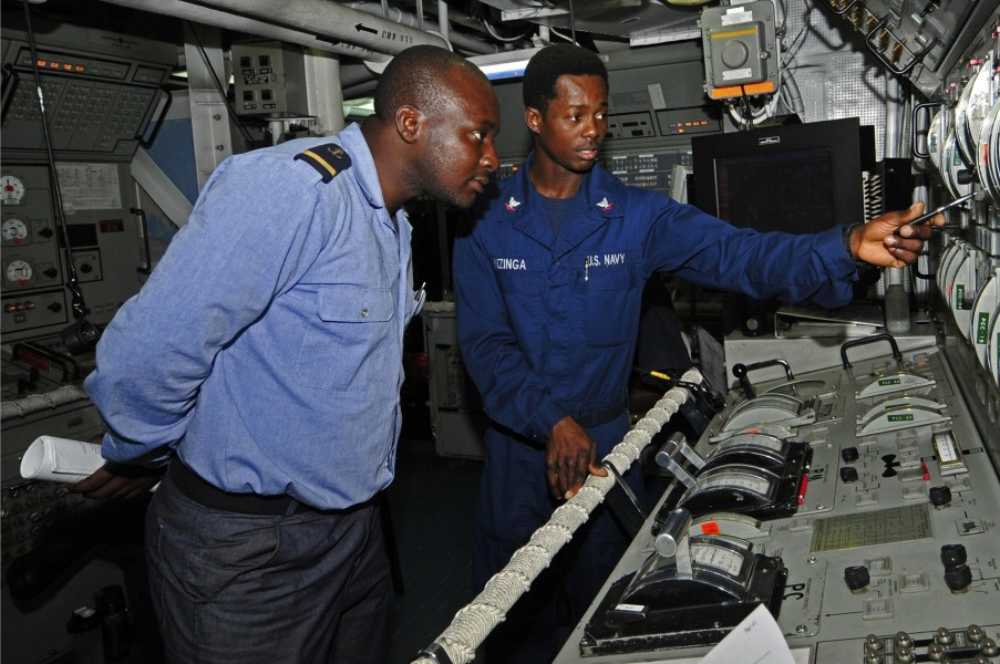 US Navy 120209-N-IZ292-079 Gas Turbine System Technician (Mechanical) 3rd Class Botha Nzinga explains the propulsion control console aboard the gui