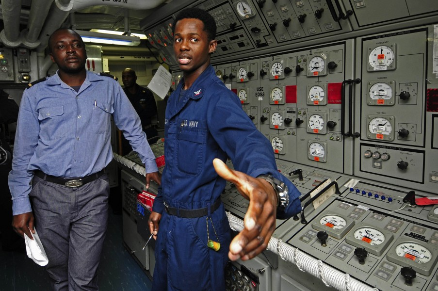 US Navy 120209-N-IZ292-102 Gas Turbine System Technician (Mechanical) 3rd Class Botha Nzinga explains the propulsion control console aboard the gui