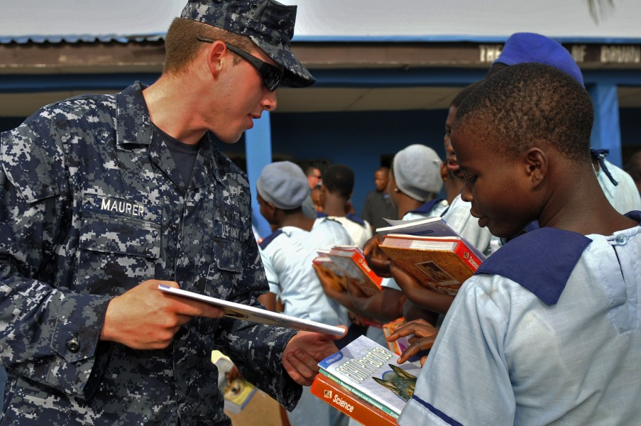 US Navy 120216-N-IZ292-060 Boatswain's Mate Seaman Joshua Maurer, assigned to the guided-missile frigate USS Simpson (FFG 56), hands books to schoo