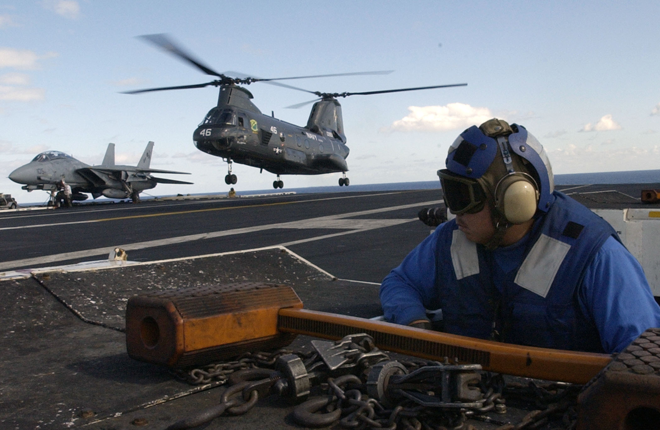 US Navy 031103-N-6713R-064 Aviation Boatswain's Mate Airman Thomas Brehm observes the landing of a CH-46 Sea Knight