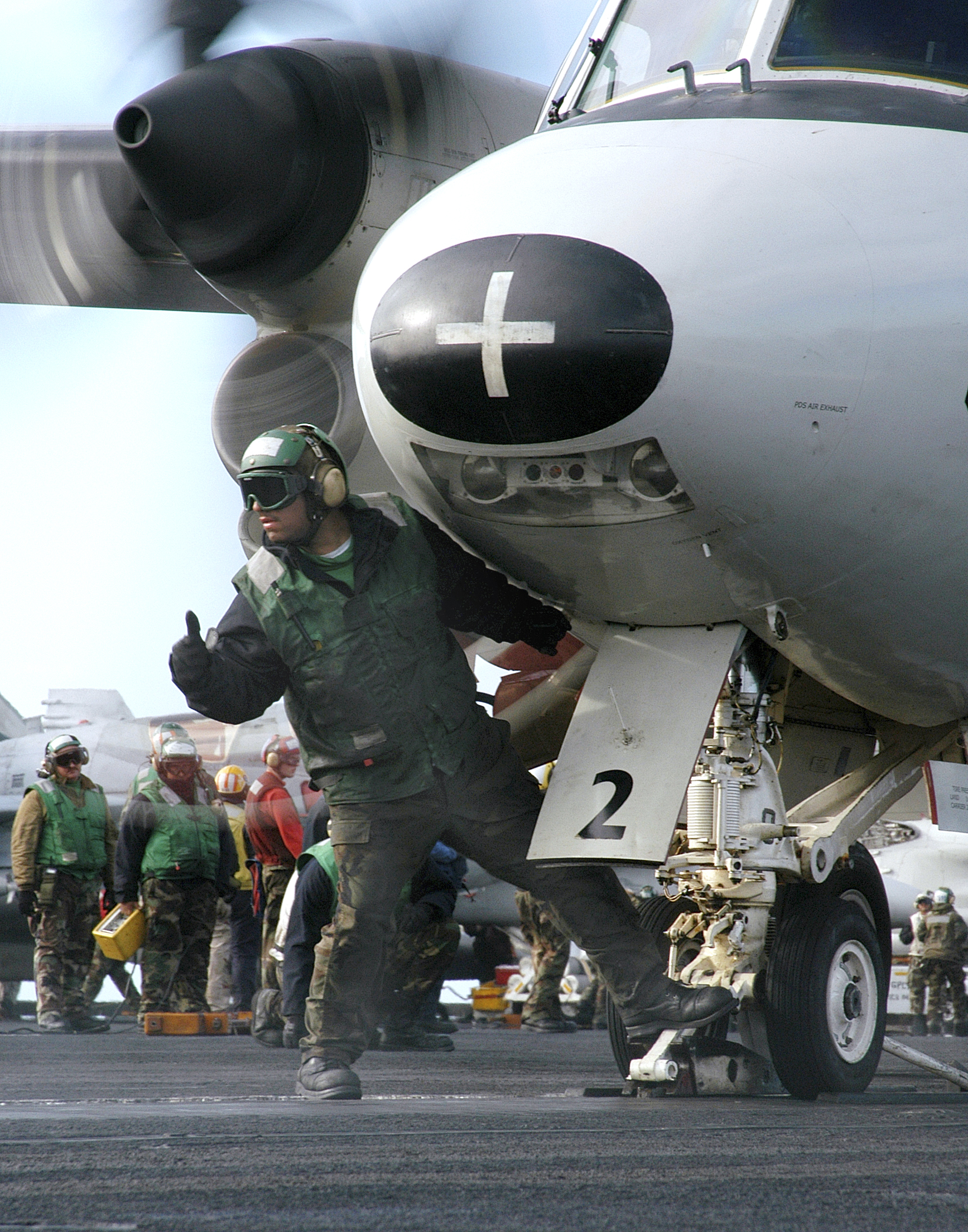 US Navy 040628-N-0119G-019 Aviation Boatswain's Mate 3rd Class David Reyes guides an E-2C Hawkeye on to one of four steam-powered catapults on the flight deck aboard USS Enterprise (CVN 65)