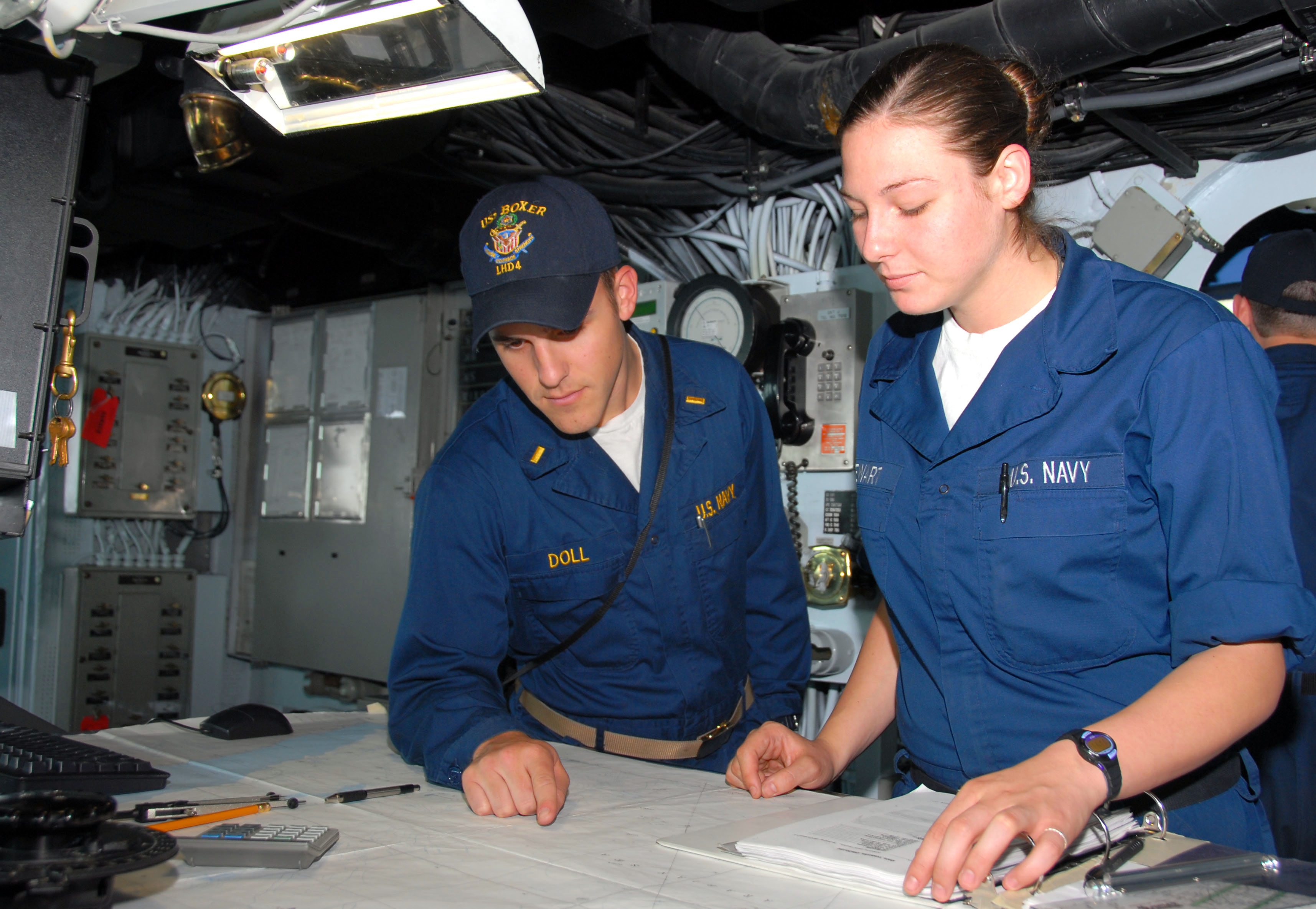 US Navy 070418-N-9689V-006 Ensign Brandon Doll, reviews the ship's position with Quartermaster Seaman Apprentice Angela Stewart